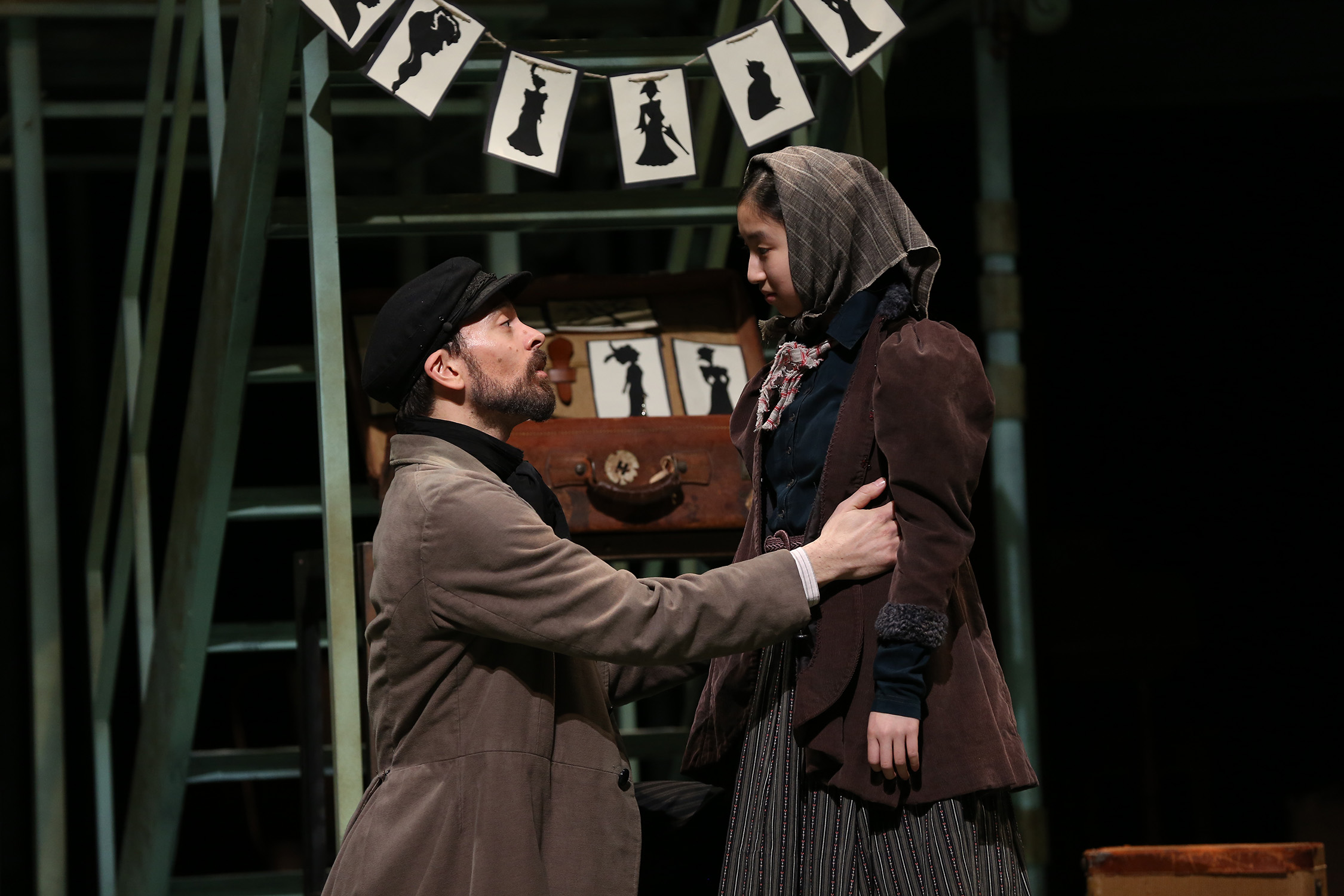 "Photo of two actors: one man (Jonathan Atkinson) and one young girl (Dulcey Pham). They are dressed as Jewish immigrants in modest clothing. The young girl wears a headscarf. They are standing near a retail kiosk where the man sells silhouette portraits. Image is from the Ford's production of ""Ragtime."""