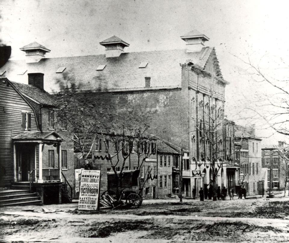 "black and white 1865 photograph looking south on 10th Street NW. Photo shows Ford's Theatre with a poster advertising a July performance of ""An Octoroon"" to benefit actress Jennie Gourley."