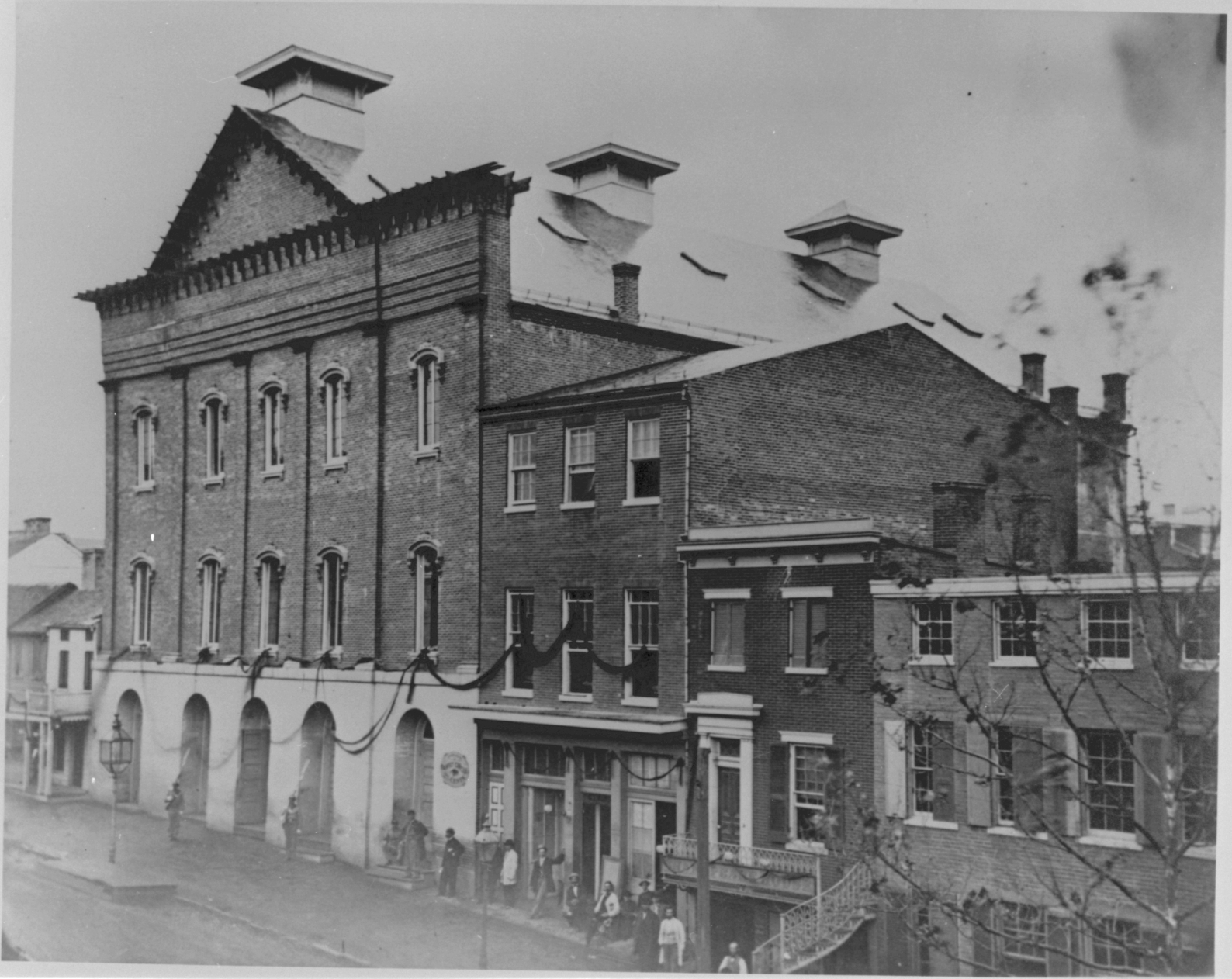 1865 black and white photograph of the exterior of Ford's Theatre in D.C. The image shows drapes of black fabric hanging horizontally between each window in mourning for the death of Abraham Lincoln.