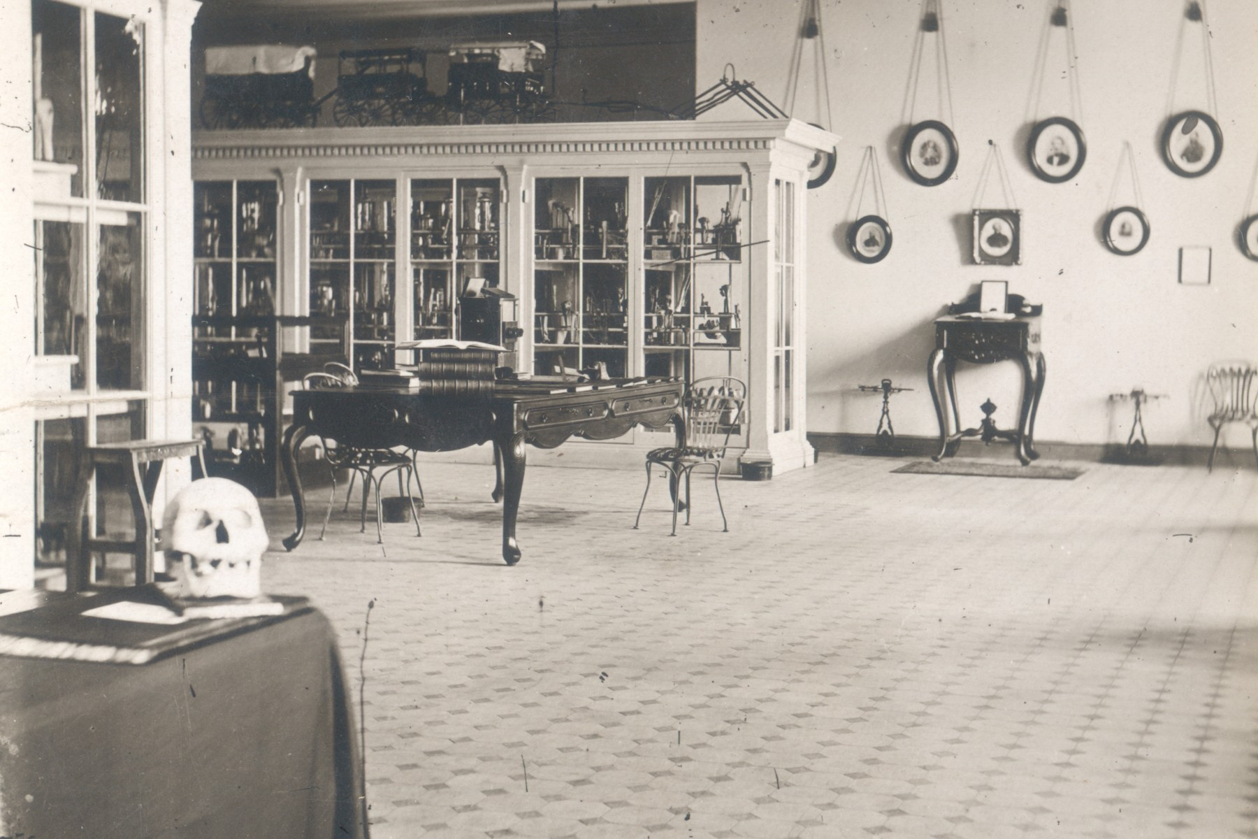 In 1867 the Army Medical Museum opened at Ford's Theatre. This black and white image shows a museum room with portraits hanging on a far wall and several central glass-windowed displace cases. The foreground of the photo features a table with a human skull on it.