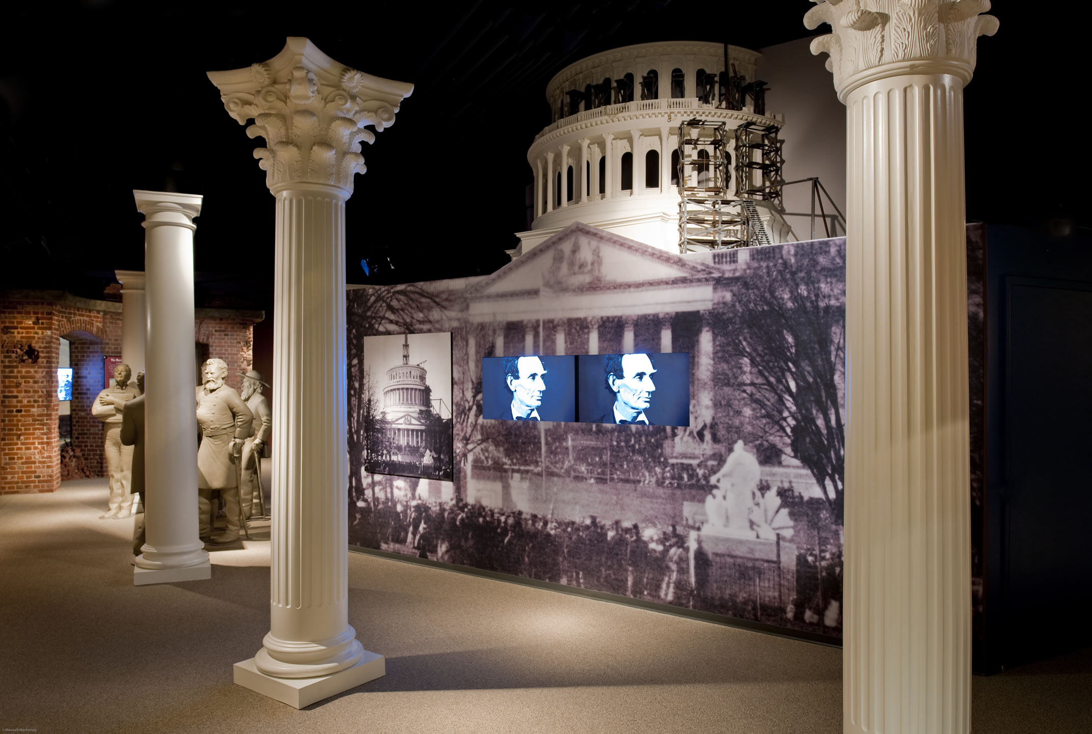 Museum exhibit of the 1860s unfinished United States Capitol dome. Lincoln's photograph is displayed on TV monitors below the Capitol dome in the exhibit.