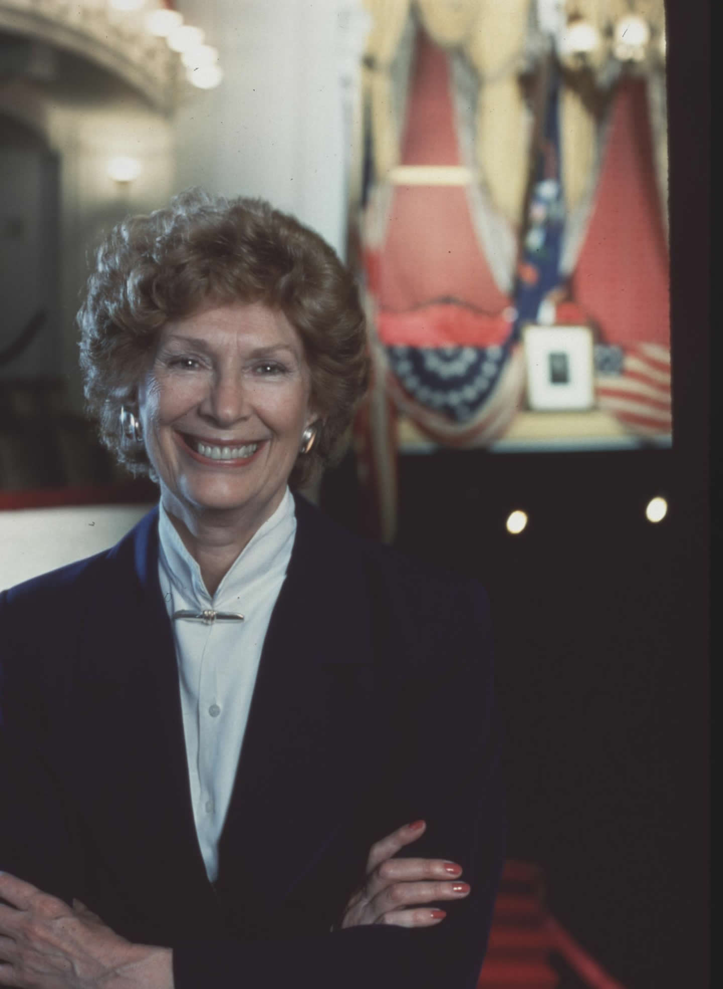 Photo of Frankie Hewitt, founder of Ford's Theatre Society. She stands in a dark suit and white blouse with arms crossed and a big smile in the blacony level of Ford's with the Presidential Box just behind her.