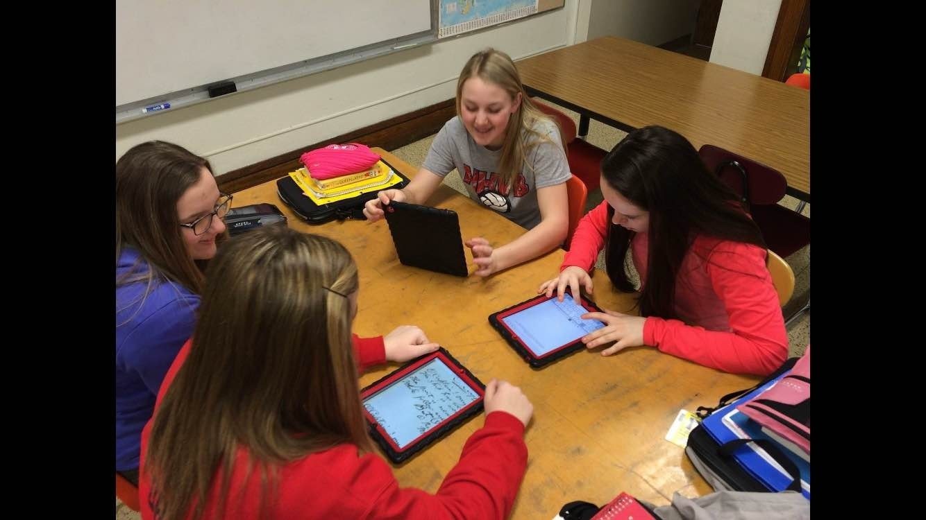 Four students sit around a table, talking and looking at tablet computer screens while transcribing historical documents.