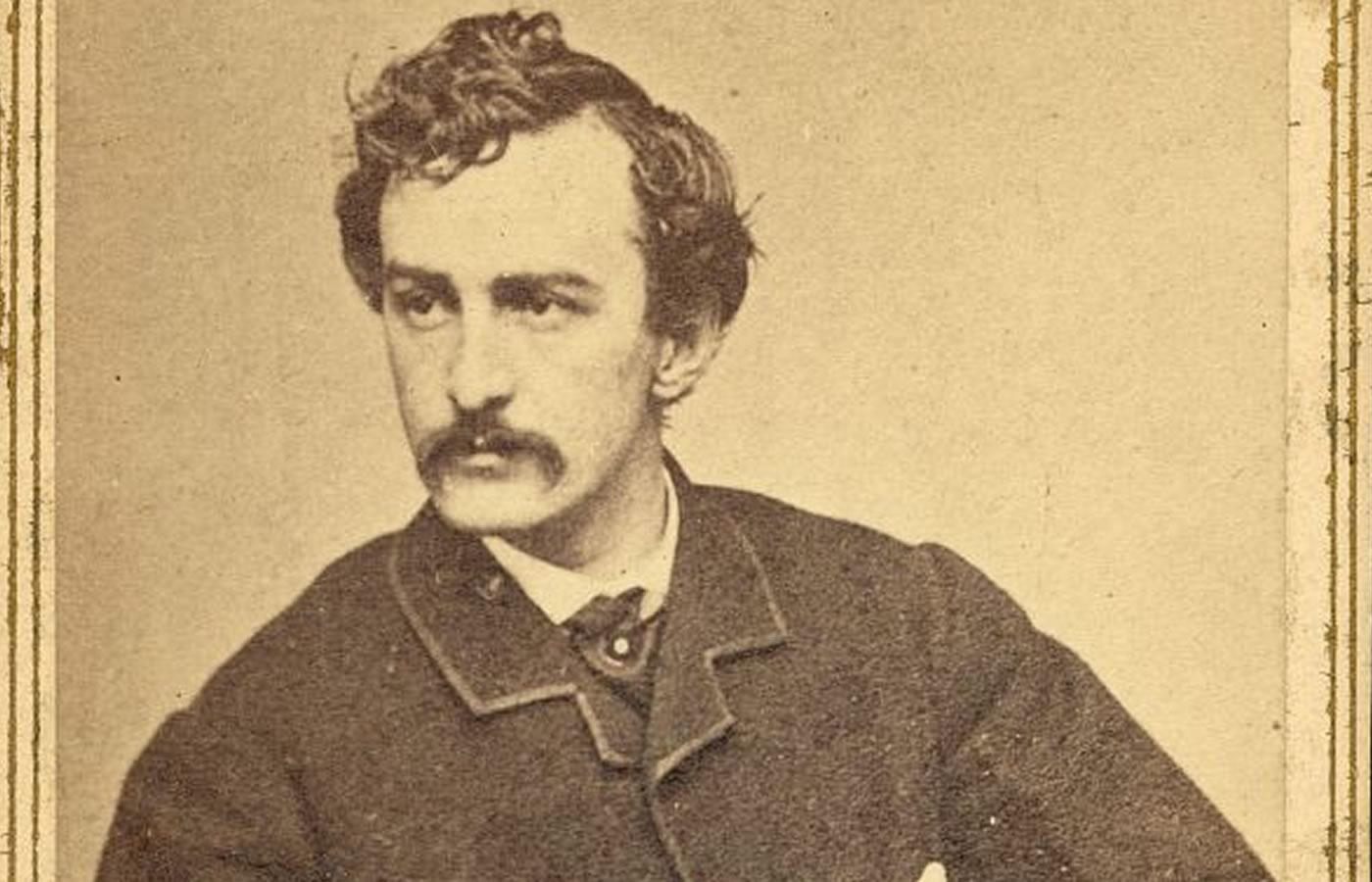 Assassin John Wilkes Booth sepia toned carte de visite photograph. Image shows the actor with hand on his hip, looking left. He has a brown bushy mustache and full head of wavy brown hair.