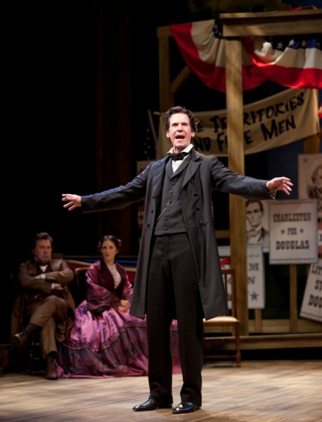 An actor portraying Abraham Lincoln stands center stage with both arms outstretched. Behind him sits a man and woman portraying Stephen and Adele Douglas.