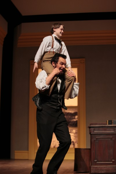 An actor dressed as Abraham Lincoln gives a shoulder-seated ride to a child actor portraying his son.