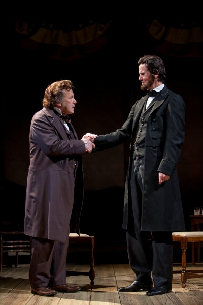 An actor portraying Stephen Douglas shakes hands with the actor portraying Abraham Lincoln.