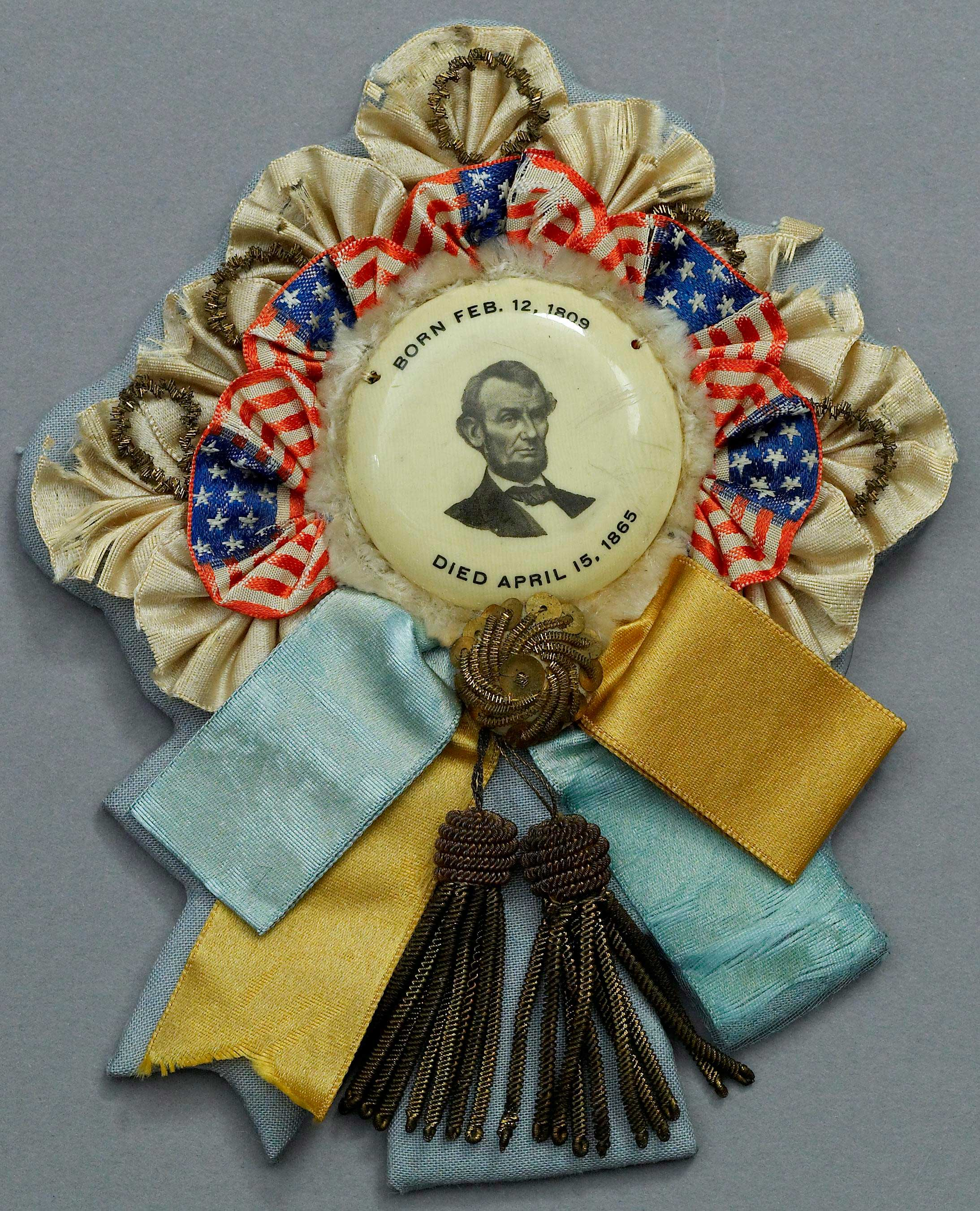 colorful mourning ribbon and badge featuring an engraving of his face from one of Lincoln's funeral train stops.