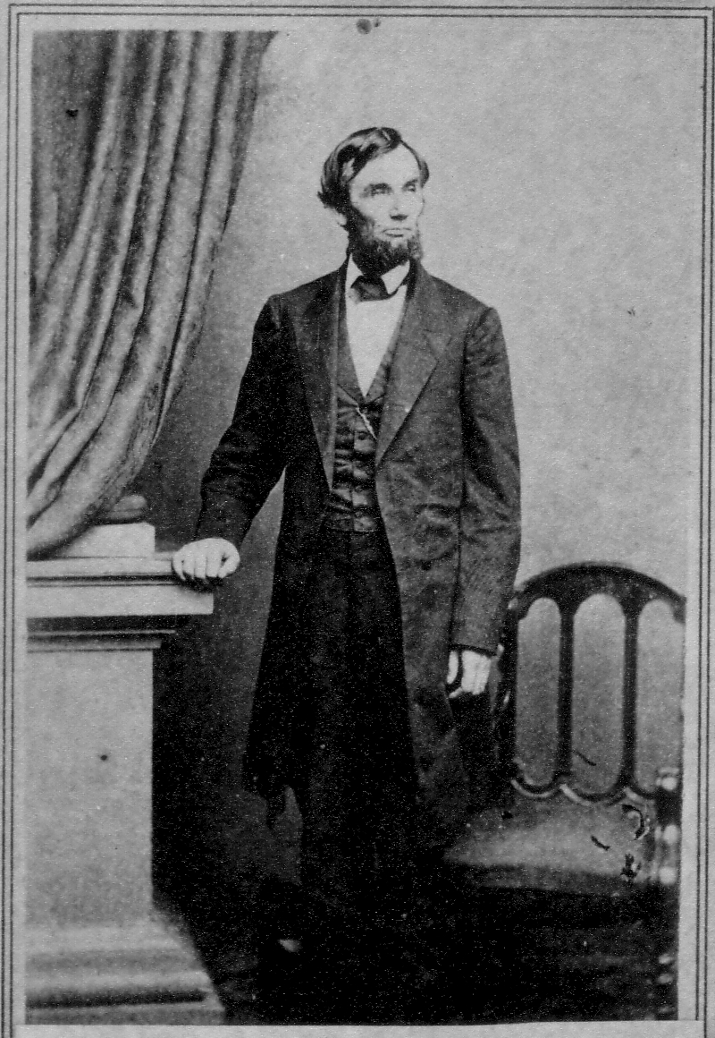 Black and white photograph of Abraham Lincoln standing with his arm resting on a nearby tabletop.