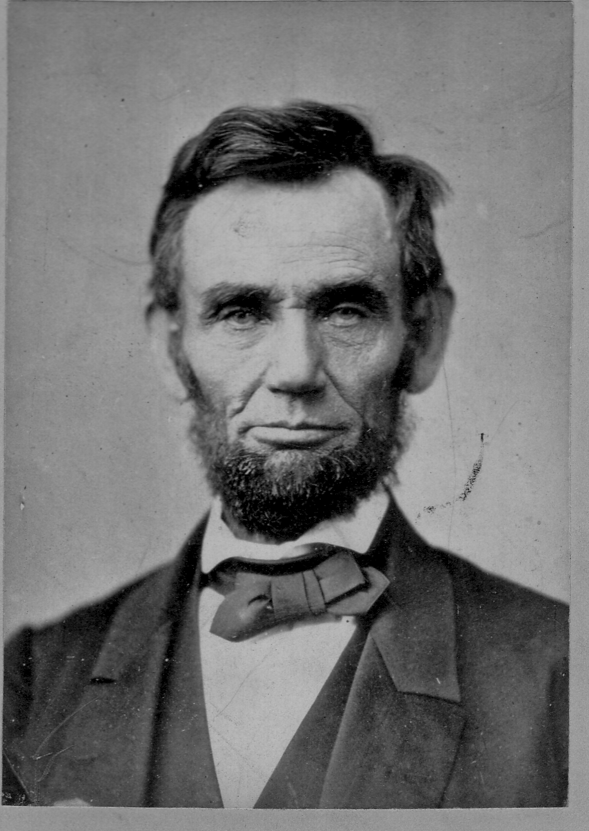 Black and white photo of President Abraham Lincoln. This head-and-shoulders portrait shows him wearing a black jacket, bowtie and white shirt.