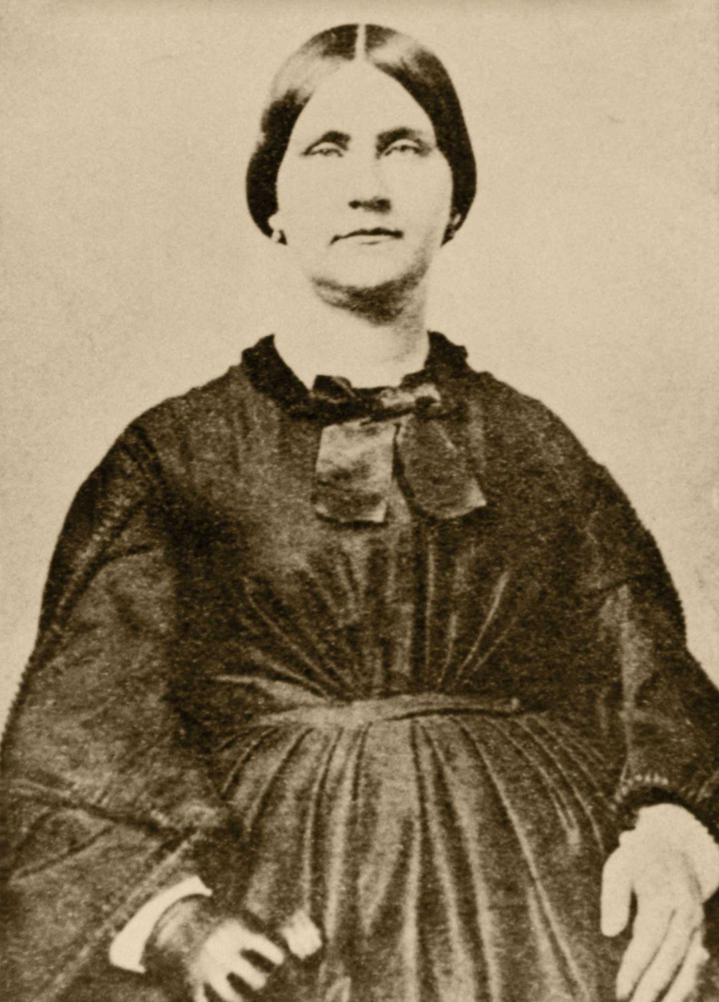 Black and white image of Mary Surratt. She wears a modest 1860s dark dress with buttons down the middle and small collar. Her hair is pulled back tightly with a part down the middle.