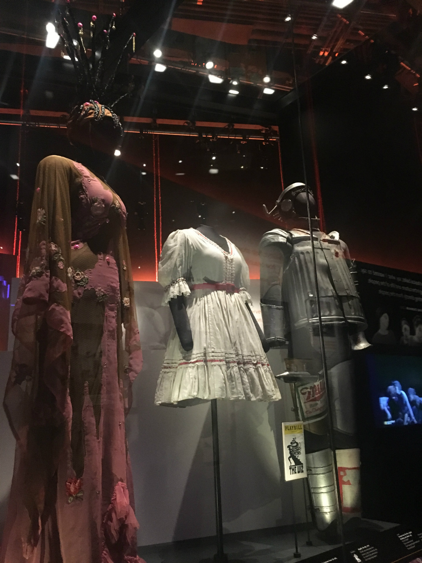 The 1970s Broadway costumes of Glinda (pale pink embroidered sheath-dress with elaborate matching hat which has 12 tree-like prongs atop it), Dorothy (knee-length white dress)  and Tinman (multiple pieces of scrap metal) from the original Broadway production.