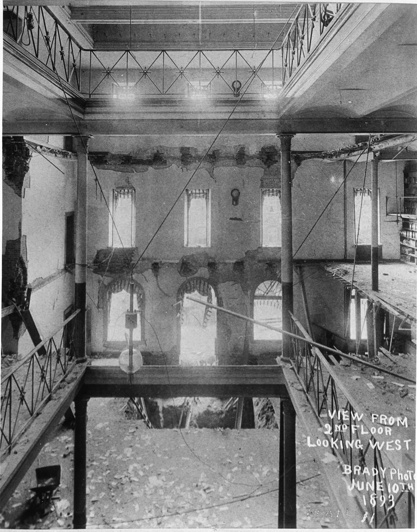 Black and white photo of a crumbled Ford's Theatre interior. Image shows the front brick facade standing with piles of rubble, wooden supports holding up walls. Image by Mathew Brady in 1893.