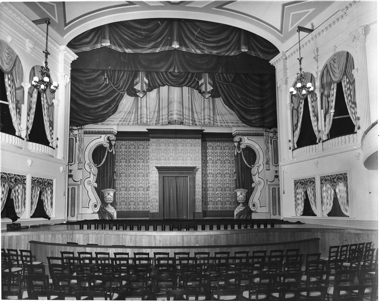 "Stage view of Ford's Theatre at its 1968 reopening. Image shows the stage itself with a large painted mural of curtains, designed to appear like the performances of ""Our American Cousin"" from April 1865"