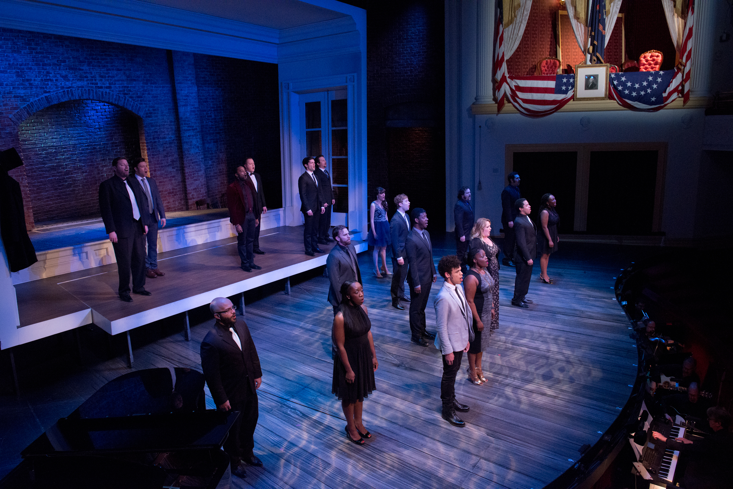A dozen actors in modern-day street clothes stand in staggered positions on the Ford's Theatre stage. They are illuminated with a moody blue light as they look out toward the hundreds of people seated in the audience. Above the actors on stage and to the right is the Presidential Box, draped with yellow curtains and it's white balcony draped with flags-- just as it was the night of Lincoln's assassination.