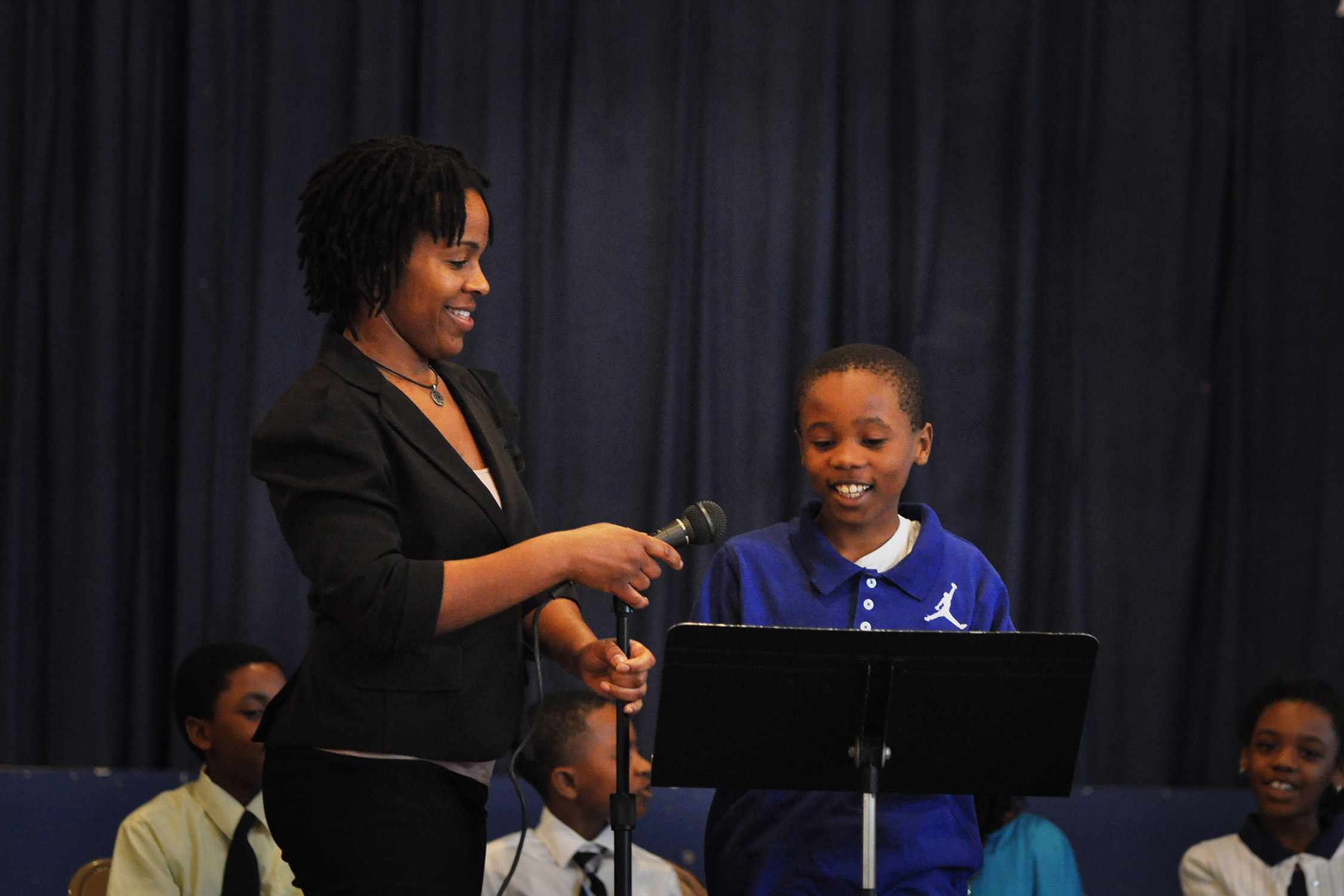 A teacher adjusts the height of a microphone for a young student to begin speaking.