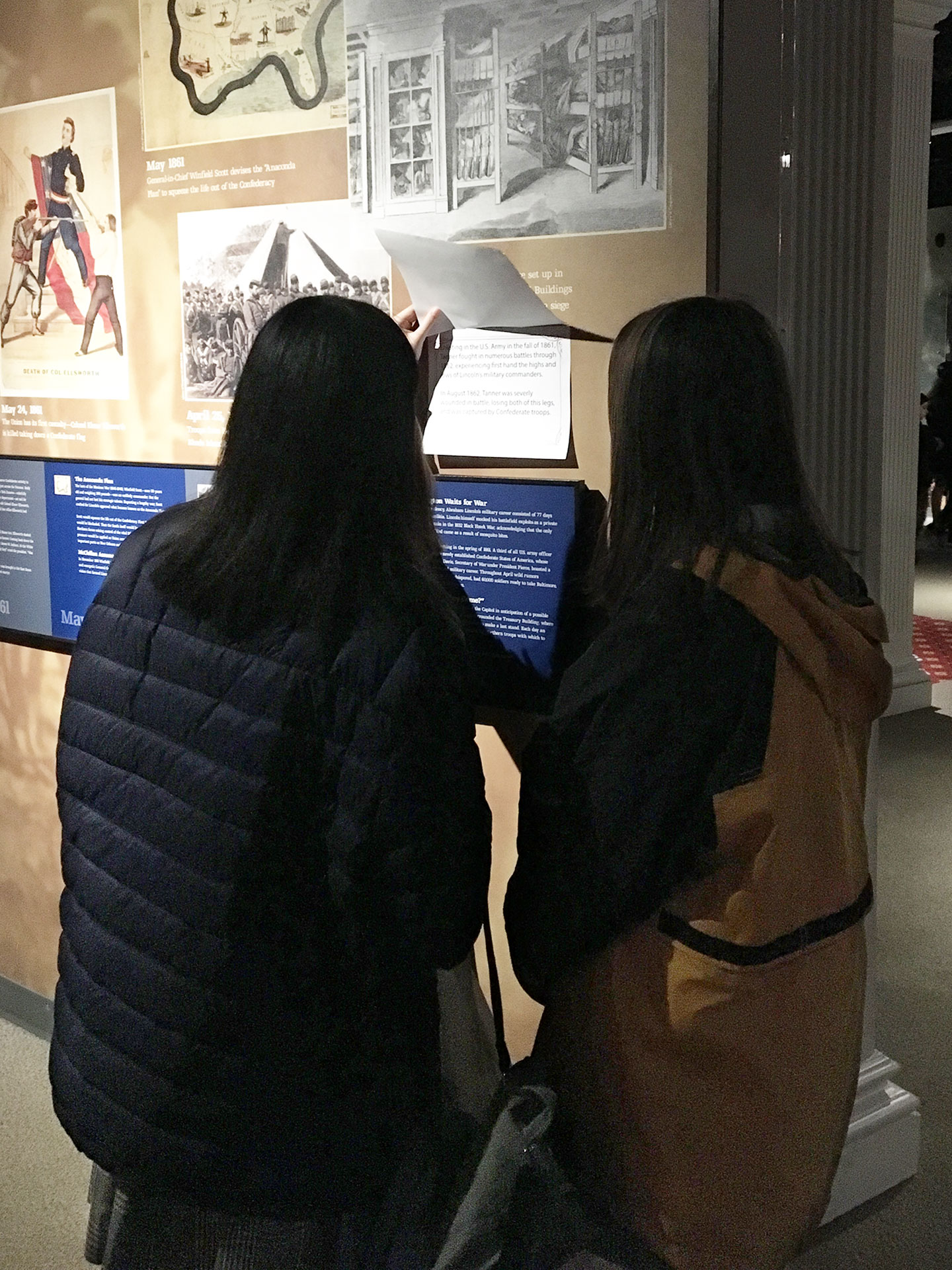 Two middle school female visitors interact with the flip-door factoids being tested in the Ford's Museum.