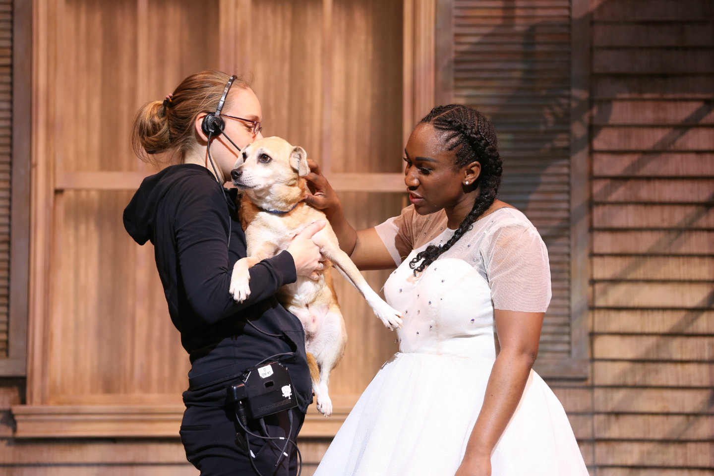 "Photo of the dog Rusty with Dorothy and a stage manager on stage during a photo shoot for ""The Wiz."""