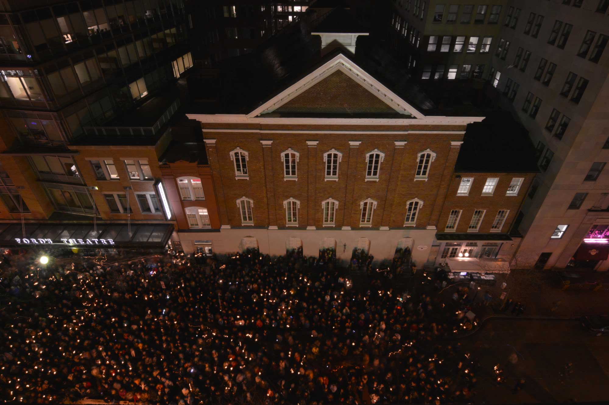 Ariel photo at the front facade of Ford's Theatre taken at night. Image shows a crowd of more than a thousand people out front holding candles. This event was part of the 150th commemoration of President Lincoln's assassination in 2015.