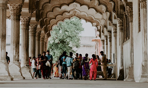 Photo of a large diverse group of people standing beneath an ornate archway on a sunny day.