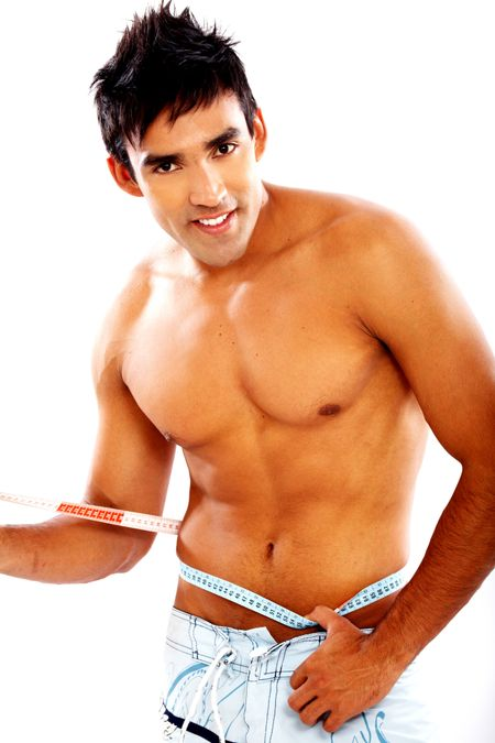 healthy man smiling and measuring his waist - isolated over a white background