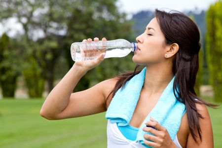 Athletic woman drinking water after exercising - outdoors