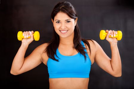 Beautiful athletic woman lifting free-weights and smiling