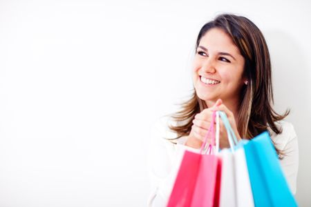 Happy shopping woman holding bags and smiling - isolated