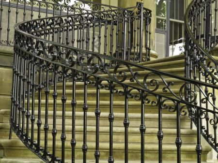 Ornate handrail of wrought iron along curved staircase to main entrance of public museum
