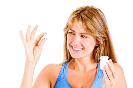 Woman taking a pill - isolated over a white background