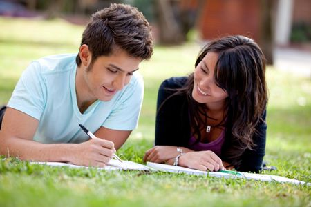 Couple of students lying outdoors and smiling