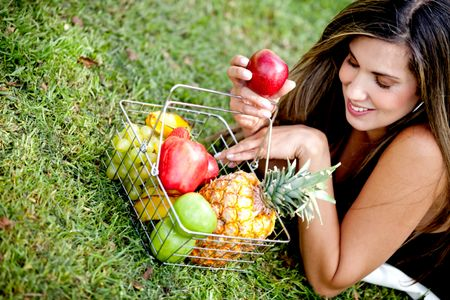 Healthy eating woman with a basket of fruits ���� outdoors