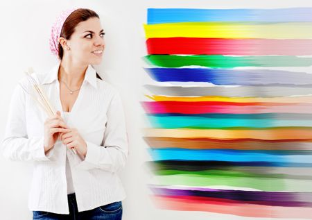 Woman painting a wall of the house and choosing from different colors