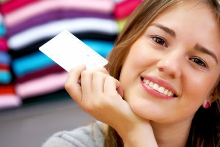 woman smiling and holding a credit card in a shop