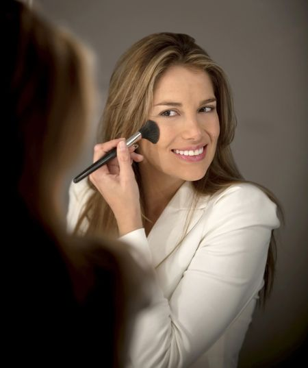 Woman putting blush on her cheeks - make up concepts