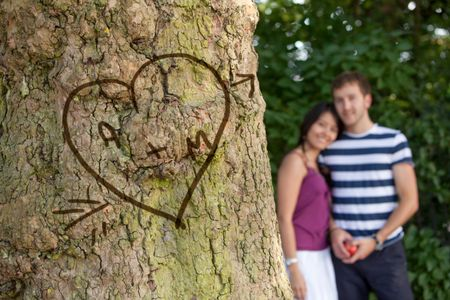 Happy couple in love with their initials carved in a tree