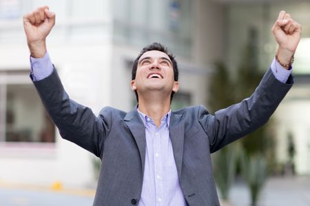 Business man celebrating with arms up and smiling