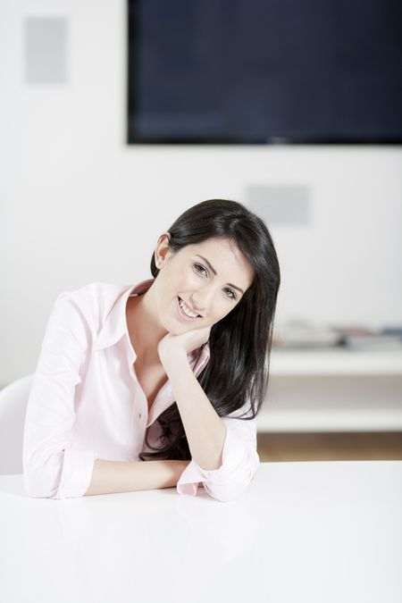 Young woman in pink shirt sitting at dining table at home