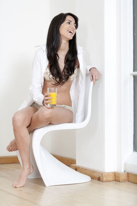 Young woman on white chair leaning against a white wall in underwear