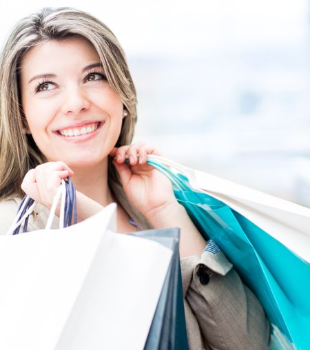 Beautiful shopping woman holding bags and smiling
