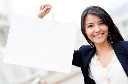 Female shopper holding a shopping bag and smiling