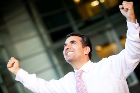 Businessman celebrating his success with arms up
