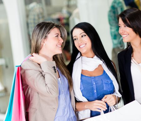 Happy shopping women at the mall holding bags