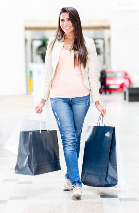 Young woman walking at the shopping center holding bags