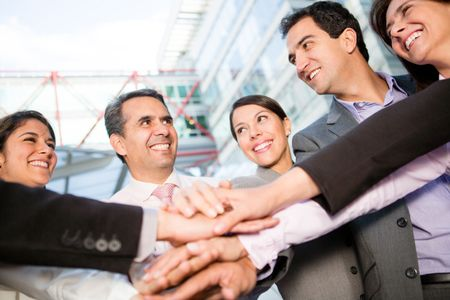 Successful business group with hands together and smiling