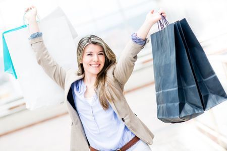 Happy shopping girl with arms up holding bags