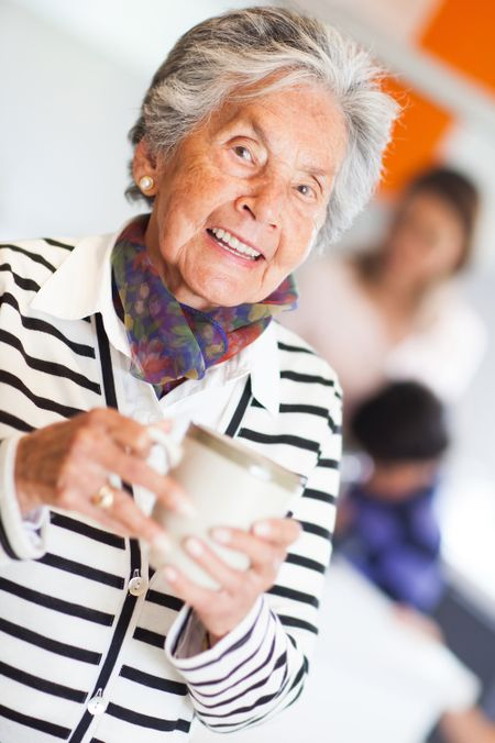 Beautiful elder woman drinking coffee at home