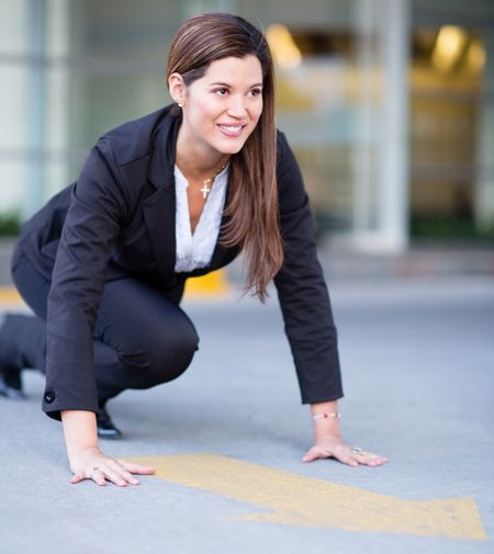 Successful business woman in position ready to race