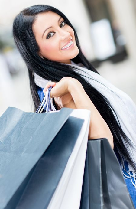 Beautiful girl holding bags at the shopping center