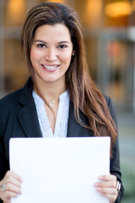 Successful businesswoman holding white documents and smiling